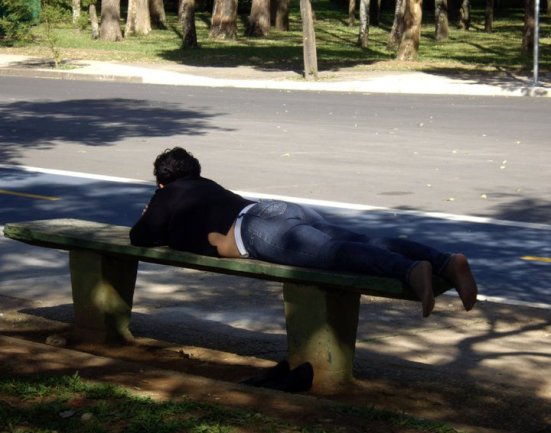 Woman, lying on a bench at Ibirapuera Park, Brazil